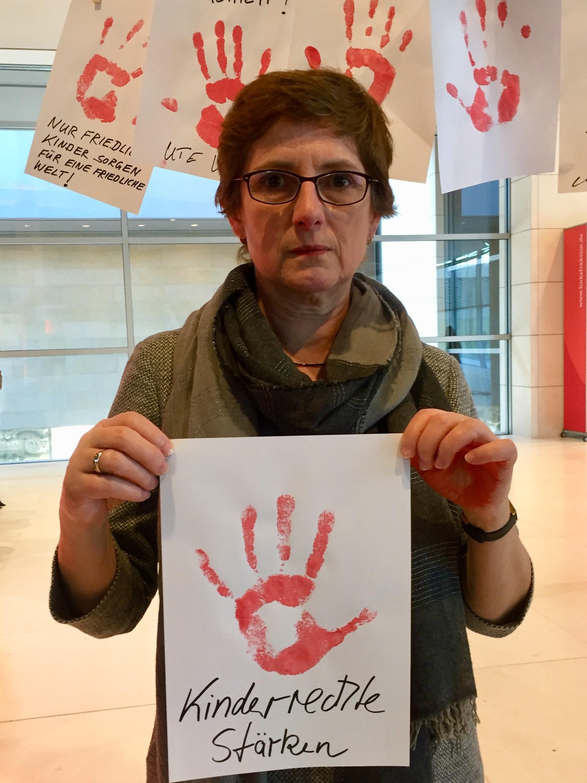 """Britta Haßelmann hält ein Papier mit einem roten Handabdruck und der Aufschrift """"Kinderrechte stärken"""" in die Kamera"""